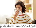 sick woman blowing nose in paper tissue at home 55574740