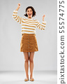 young woman in striped pullover, skirt and shoes 55574775