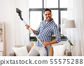 man in headphones with vacuum cleaner at home 55575288