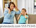 mother and daughter in headphones listen to music 55575345