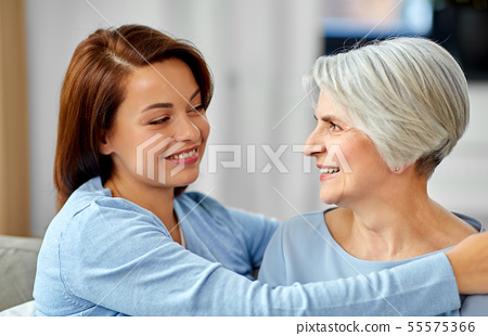 senior mother with adult daughter hugging at home 55575366
