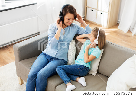 mother and daughter in headphones listen to music 55575378