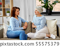 senior mother talking to adult daughter at home 55575379