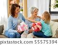 granddaughter hugging and greeting grandmother 55575394