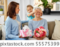 mother and daughter greeting grandmother at home 55575399