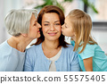 mother and daughter kissing happy grandmother 55575405
