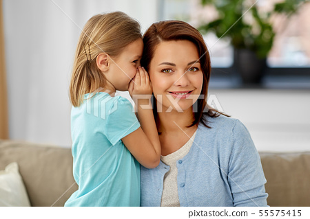 daughter whispering secret to mother at home 55575415