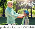 old man helping boy with bike helmet at park 55575444