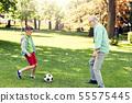 old man and boy playing football at summer park 55575445