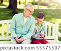 old man and boy with smartphones at summer park 55575507