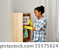 african american woman dusting and cleaning home 55575624