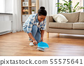 happy woman with brush and dustpan sweeping floor 55575641