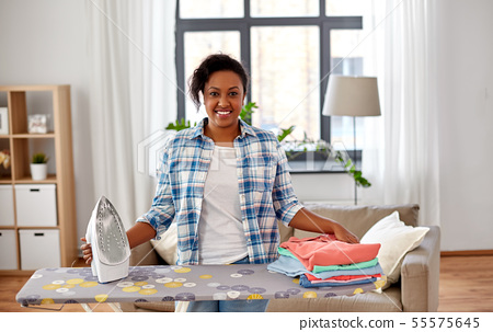 african american woman with ironed clothes at home 55575645