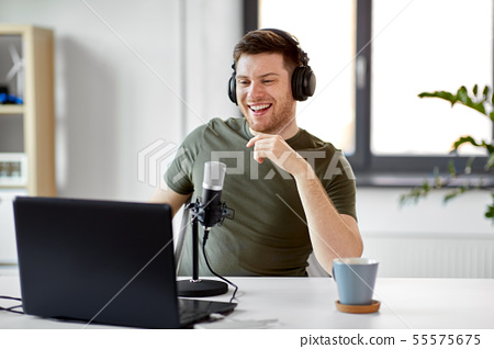 man with laptop and microphone at home office 55575675