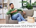 happy indian man drinking takeaway coffee at home 55575677