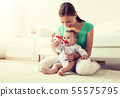 mother with spoon feeding little baby at home 55575795
