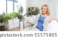woman with remote control watching tv at home 55575805