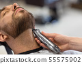 man and barber with trimmer cutting beard at salon 55575902