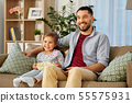 happy father and daughter watching tv at home 55575931