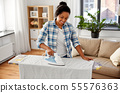 african american woman ironing bed linen at home 55576363