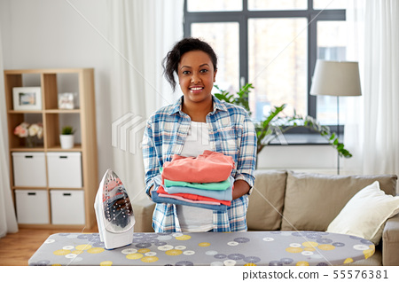 african american woman with ironed clothes at home 55576381