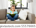 little girl with diary sitting on sofa at home 55576665