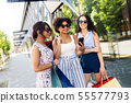 women with shopping bags taking selfie in city 55577793