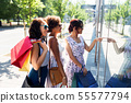 women with shopping bags looking at shop window 55577794