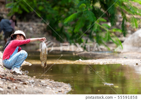 Asian girl collecting garbage and plastic on the r 55591858