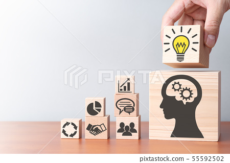 業務知識和解決方案。裝載在桌上的積木的手。 55592502