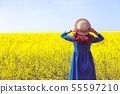 girl walking in a field of yellow rapeseed 55597210
