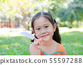 Adorable little Asian child girl fold a piece of 55597288