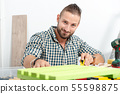 young handyman measuring with tape 55598875