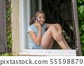 young teenage girl sitting near the window is 55598879