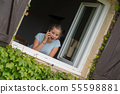 young teenage girl near the window is using a 55598881