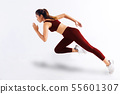 Side view of slim Asian female in red sportswear sprinting fast against white background 55601307