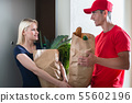 Female customer receiving the grocery delivery 55602196
