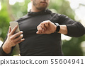 Male athlete using fitness app on his smartwatch 55604941