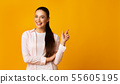 Positive Girl Pointing Finger At Free Space On Yellow Background 55605195