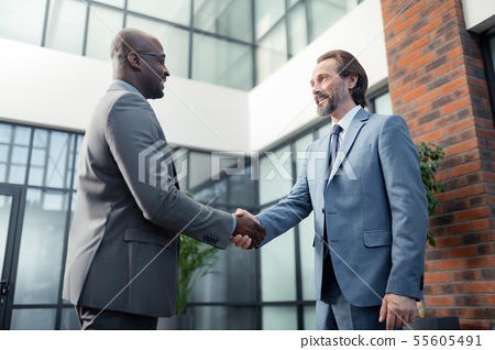Man smiling while meeting his African-American investor 55605491