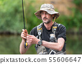 Portrait of mid adult fisherman on river, relaxing and fishing trouts. 55606647