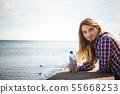 Man long hair relaxing by seaside drinking water 55668253