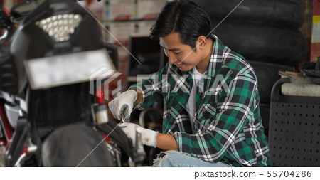 Cropped view of motorcycle mechanic using a wrench 55704286