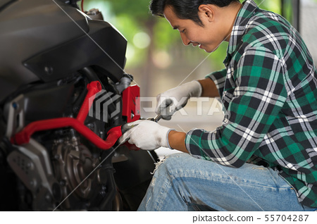 Cropped view of motorcycle mechanic using a wrench 55704287