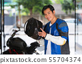 Handsome man carrying a motorcycle helmet 55704374