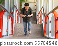 Man walking up stairs and using smartphone in city 55704548