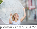 Beautiful young blonde girl holding umbrella in 55704755