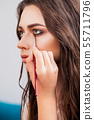beauty and makeup concept - closeup portrait of beautiful woman getting professional make-up with 55711796