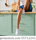Female legs in socks on kitchen table 55712241