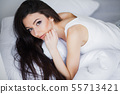 Relaxing On Bed During Weekend. Beautiful Woman Relaxing on a Bed and Looking Happy 55713421